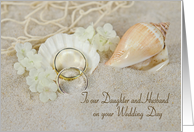 Daughter's wedding-rings in beach sand with seashells and net card