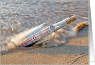 Merry Christmas message in a bottle on the beach card