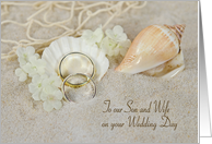 Son's wedding-rings in beach sand with seashells and net card