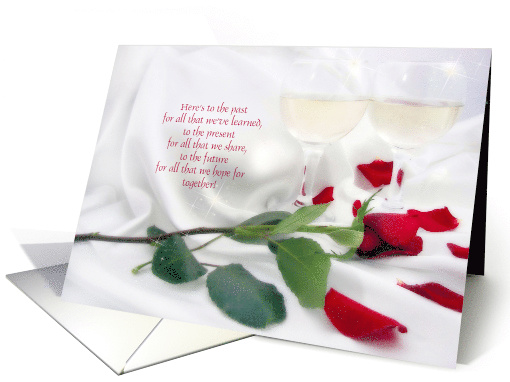 anniversary celebration with red rose and wine glasses on satin card