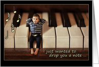 Thinking of you, miniature baby on piano keyboard, note card