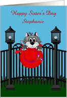 Sister's Day Custom Name Card with a Cat on a Fence Holding a Red Hat card